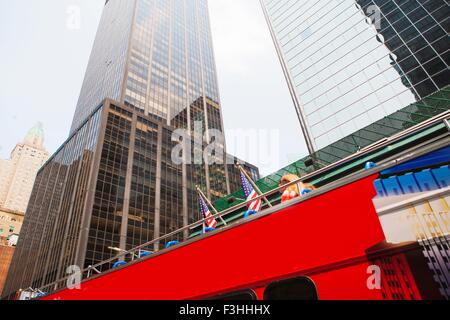 Sight seeing bus with office buildings, low angle view, New York, USA - Stock Photo