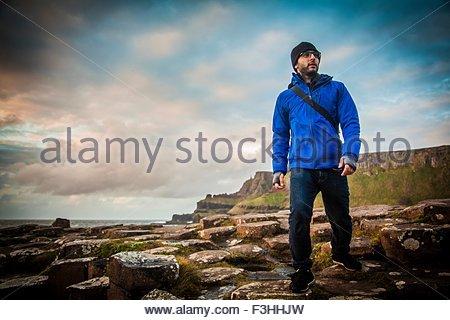 Male hiker on rocks, Giants Causeway, Bushmills, County Antrim, Northern Ireland - Stock Photo