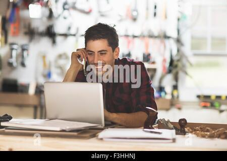 Young man sitting at desk in workshop talking on phone using laptop smiling