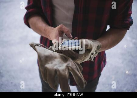 High angle cropped view of young mans hands wearing protective gloves using smartphone - Stock Photo