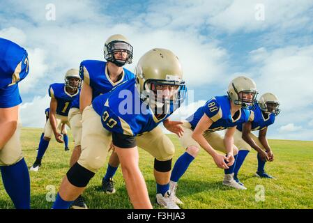 Team of teenage and adult American football players hunkering down on practice field - Stock Photo