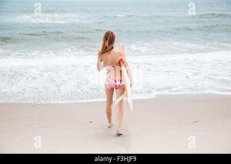 Mid adult woman walking towards sea, holding surfboard, rear view - Stock Photo