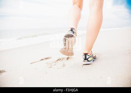 Mid adult woman walking on beach, rear view, low section - Stock Photo