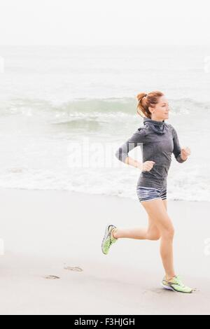 Mid adult woman running along beach - Stock Photo