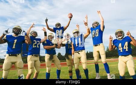 Teenage and young male American football team celebrating on soccer pitch - Stock Photo