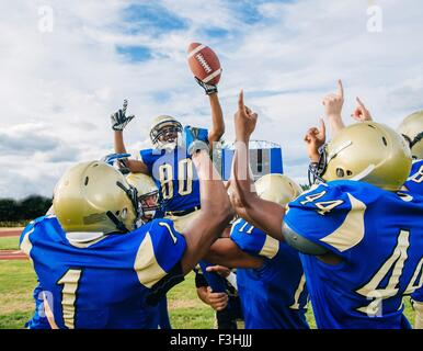 Teenage and young male American football team celebrating victory on soccer pitch - Stock Photo
