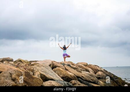 Rear view of mature woman practicing yoga on coastal rocks, - Stock Photo