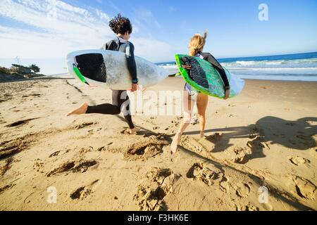 Couple running towards sea, carrying surfboards, rear view - Stock Photo
