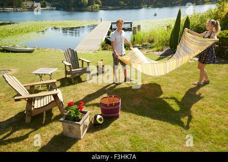 Couple laying picnic blanket on grass, lake in background, Seattle, Washington, USA - Stock Photo