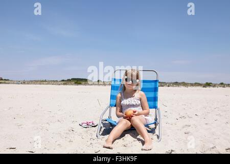 Portrait of girl wearing sunglasses sitting on deck chair at beach - Stock Photo