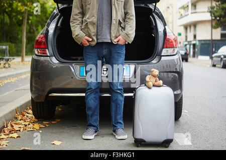 Mid adult man standing beside car with open boot, suitcase in road - Stock Photo