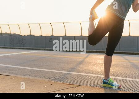 Mid adult woman, working out, stretching, outdoors, low section - Stock Photo
