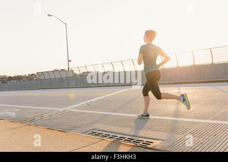 Mid adult woman, running, outdoors, rear view - Stock Photo