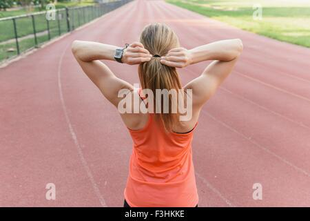 Young woman preparing to run on sports track, rear view - Stock Photo