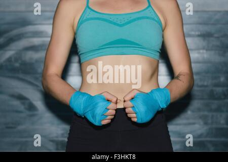 Young woman wearing sports clothing, mid section - Stock Photo