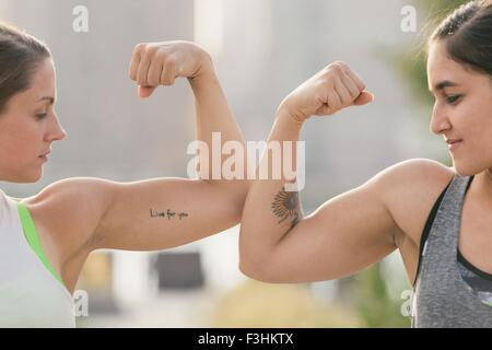 Two friends comparing bicep muscles - Stock Photo