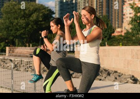 Two friends exercising together, doing leg lifts outdoors - Stock Photo