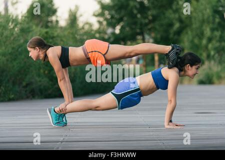 Two friends exercising together and helping each other balancing on back doing push ups - Stock Photo