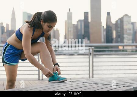 Young woman in running clothes next to river tying her shoelace - Stock Photo