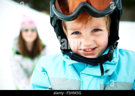 Portrait of male toddler wearing ski helmet - Stock Photo