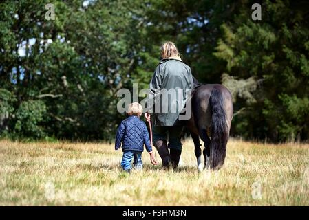 Rear view of mother and son walking pony in field - Stock Photo