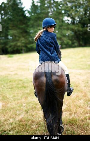 Rear view of girl horseback riding in field - Stock Photo