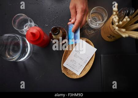 Overhead view of man paying with credit card - Stock Photo