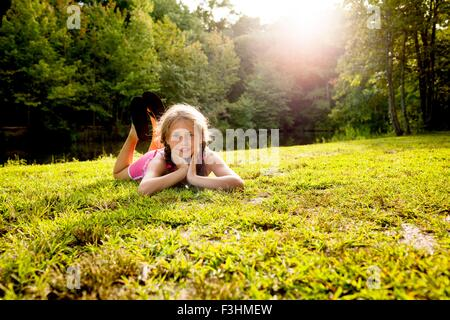 Surface level view of girl lying on front on grass looking at camera - Stock Photo