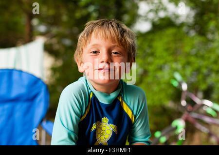 Portrait of boy wearing swimwear looking at camera smiling - Stock Photo