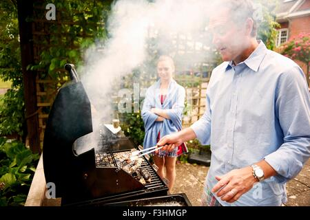 Daughter watching father cook sea food on barbecue - Stock Photo