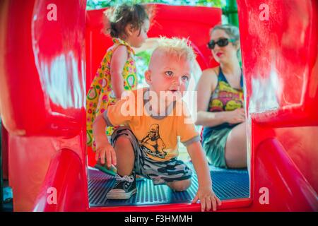 Mother and children playing on red playground slide - Stock Photo