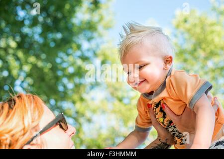 Low angle view of mother holding up smiling baby boy - Stock Photo
