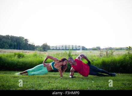 Young couple training doing side push ups in unity - Stock Photo