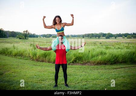 Portrait of young man training with girlfriend on his shoulders