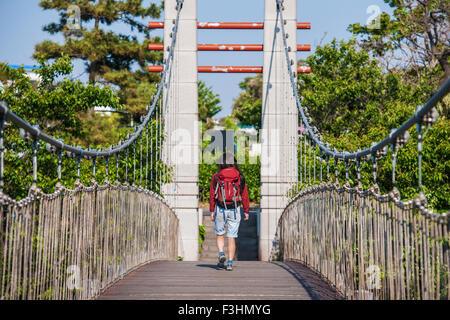 Woman walking over a suspension bridge over river Yongyeon in Jeju Si on Jeju Island - Stock Photo