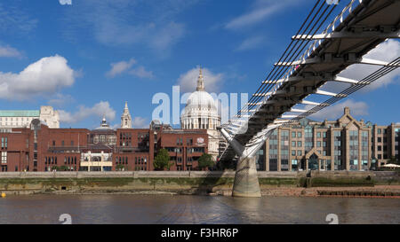 Millennium Bridge (Wobbly Bridge) and River Thames at low tide with St Paul's Cathedral at the focal point City - Stock Photo