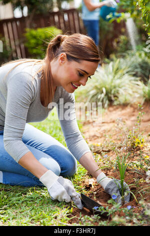 happy young woman planting in home garden - Stock Photo