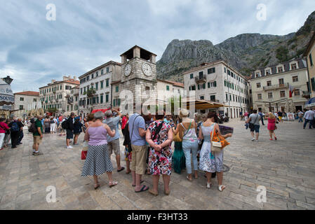 Tourists on Square of Arms under the Clock Tower, Kotor, Montenegro - Stock Photo
