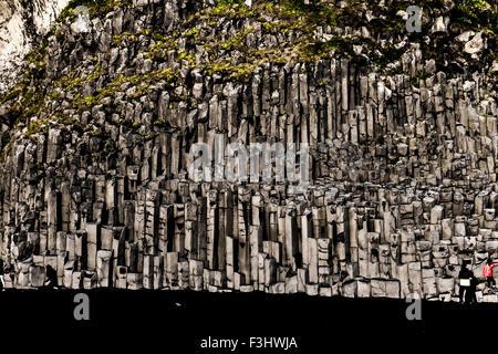 Basalt geometrical column rock formations on the black sand volcanic Kirkjufjara beach near Vik, Iceland