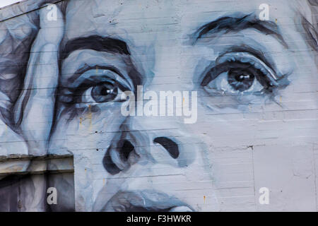 A large graffiti painted ladies face on an aged, white concrete wall - Stock Photo