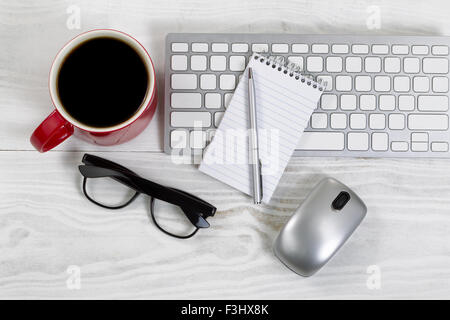 White desktop with red coffee cup, partial keyboard, mouse, reading glasses, paper and pen. - Stock Photo