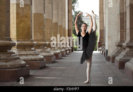 Girl ballerina flats standing on tiptoes on the street - Stock Photo