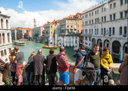 VENICE, ITALY - APRIL 24, 2013: Tourists take in the view of the Grand Canal from the Rialto Bridge. - Stock Photo