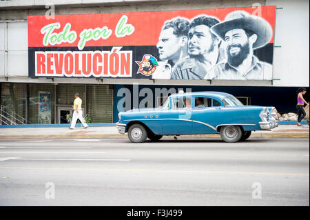 HAVANA, CUBA - JUNE 12, 2011: Vintage American taxi car passes below billboard promoting Communist propaganda on - Stock Photo