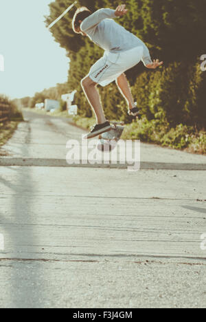 Young man skateboarding in the summer - Stock Photo