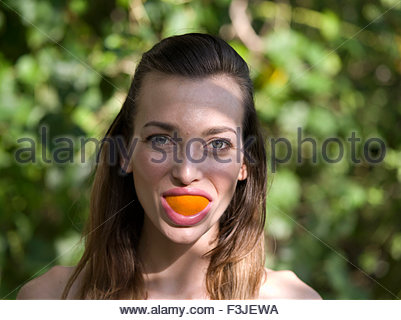 Young Woman Messing About Eating Oranges - Stock Photo