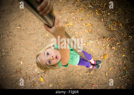 Child Girl climbs on a pole at the playground, sliding, kid playing - Stock Photo