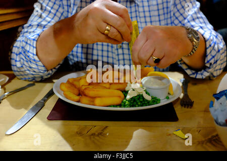 close up of man's hands pouring tartar sauce on scampi and chips pub food peas mayonnaise wooden table The Duke - Stock Photo