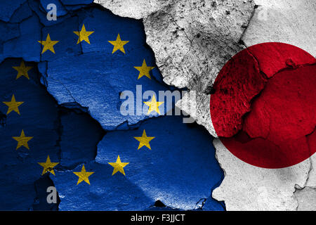 flags of European union and Japan painted on cracked wall - Stock Photo