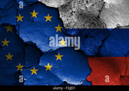 flags of European union and Russia painted on cracked wall - Stock Photo